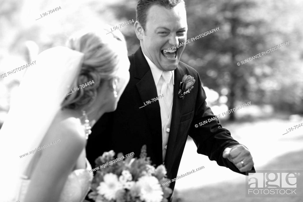 Stock Photo: elated groom stealing away with his bride after the wedding ceremony.