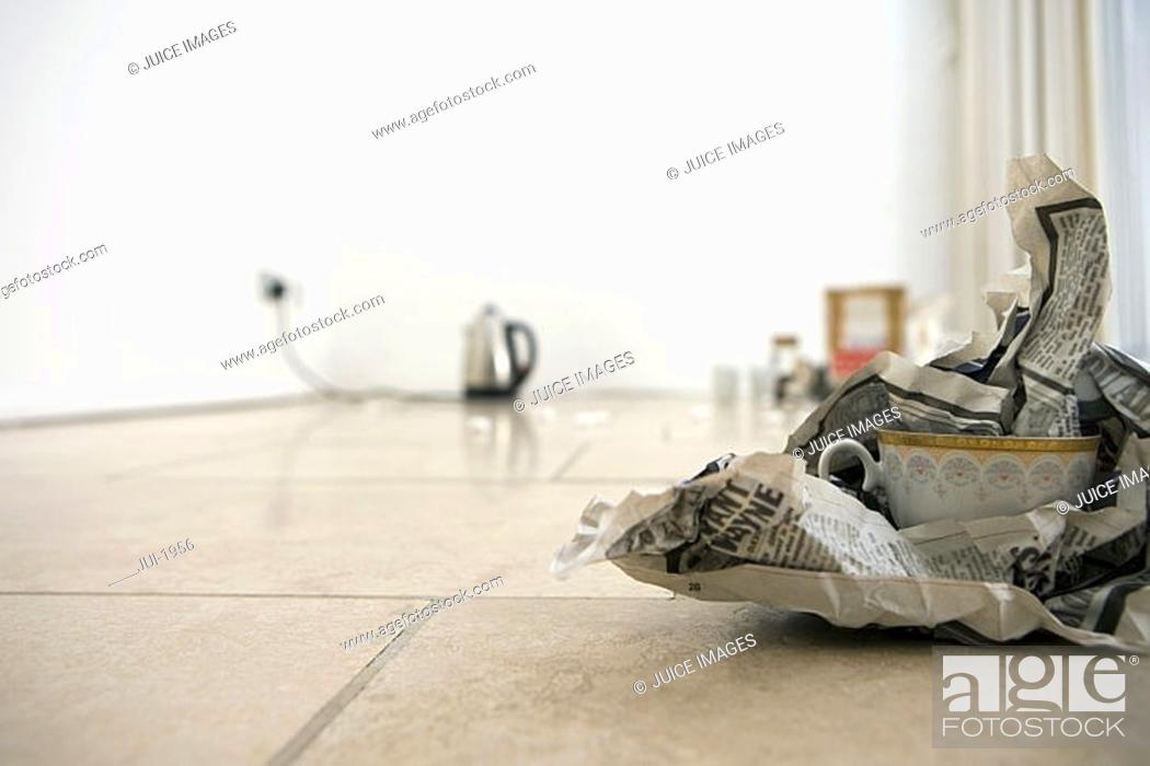 Stock Photo: China cup wrapped in newspaper on living room floor, close-up, surface level, focus on foreground.