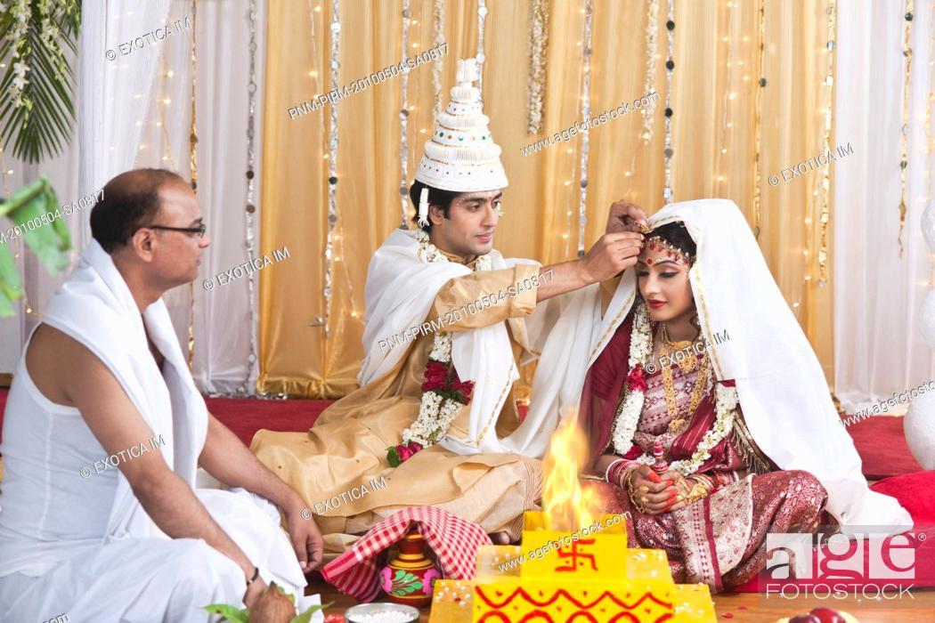 Couple performing Sindoor Daan ceremony in Bengali wedding, Stock