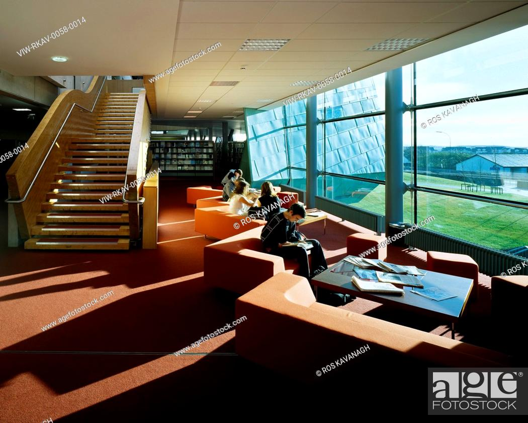 Stock Photo: Galway-Mayo Institute of Technology, Galway, Ireland. Architect: Murray O'Laoire, 2003. View of seating area in library showing stairs, shelving, seating.