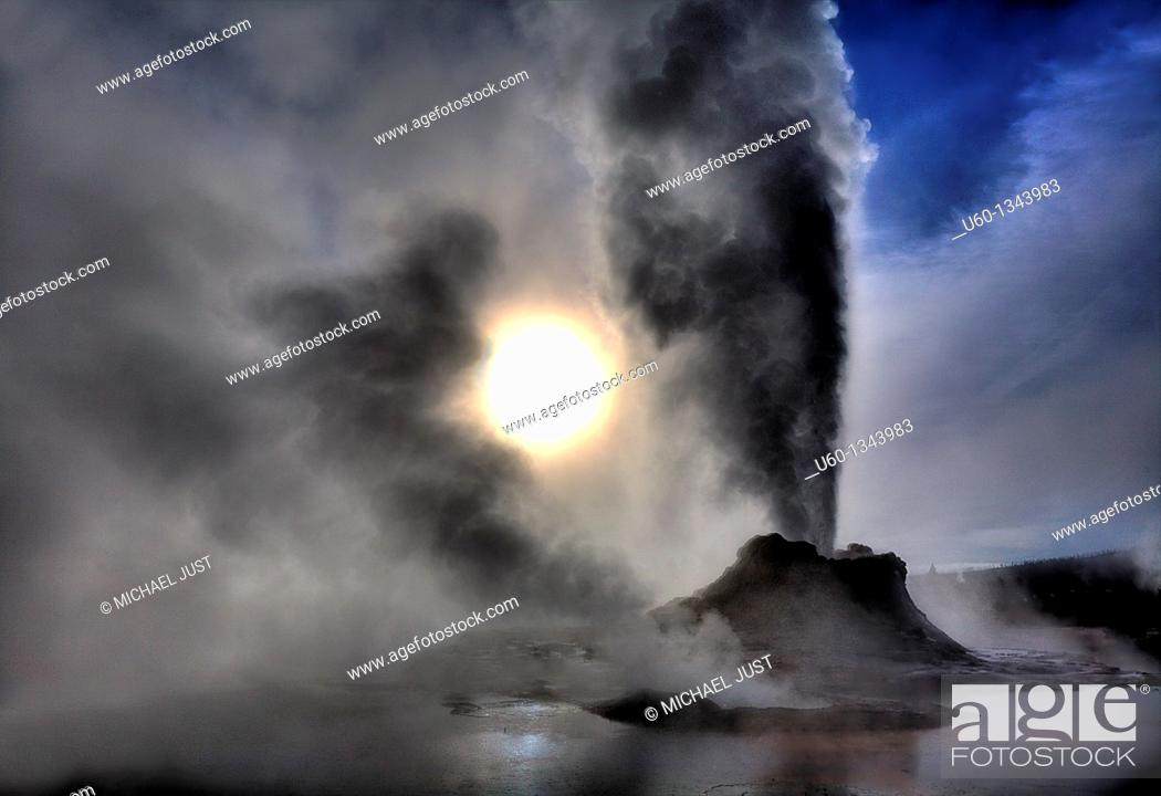 Stock Photo: Castle Geyser erupts under a bright sky during winter at Yellowstone National Park.
