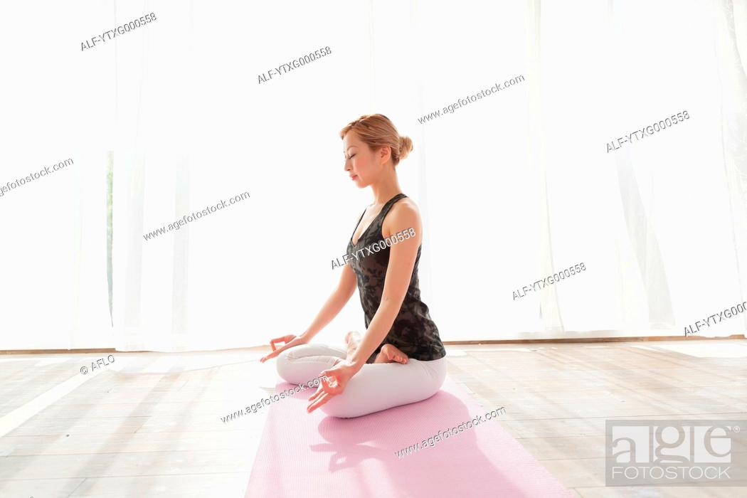 Photo de stock: Attractive young Japanese practicing yoga in an airy room.