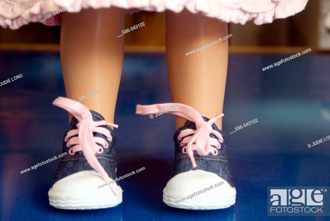 Stock Photo: Toddler girl sneaker shoes on a store window mannequin.