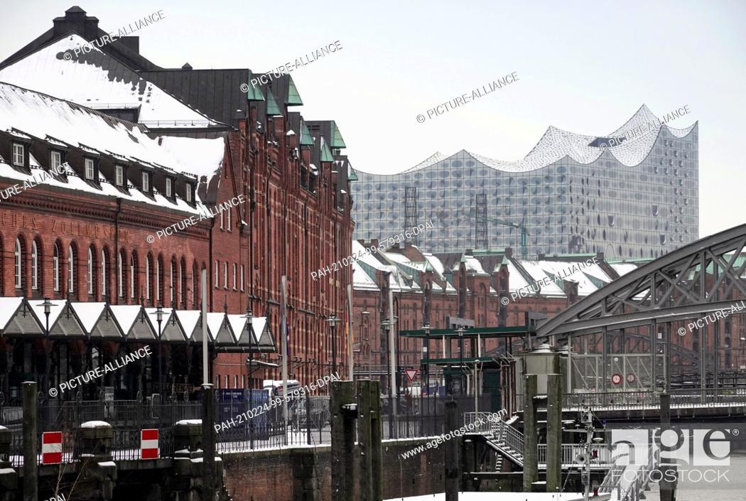 Stock Photo: 01 February 2021, Hamburg: Houses of the historic Speicherstadt on the Zollkanal against the backdrop of the Elbphilharmonie.