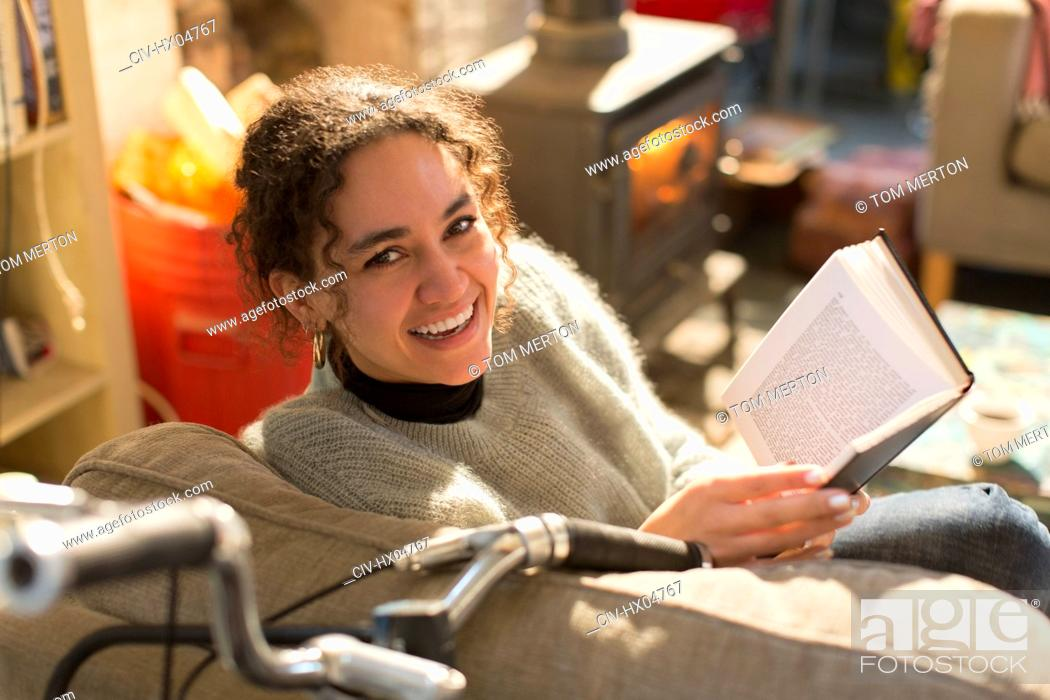 Stock Photo: Portrait smiling, happy young woman reading book in armchair.