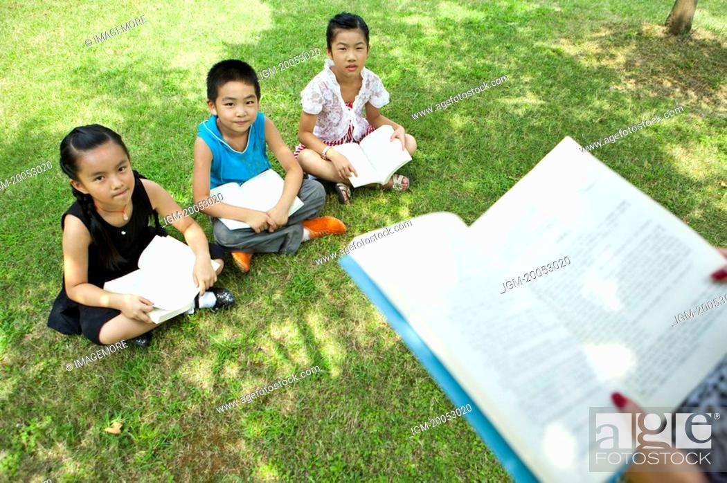 Stock Photo: Three children sitting on the lawn, reading together.