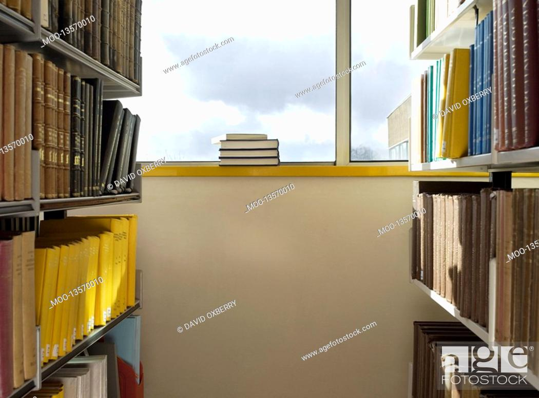 Stock Photo: Library interior pile of books on windowsill.
