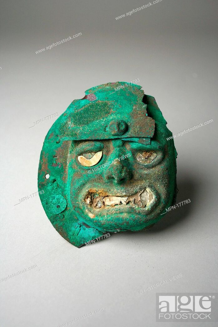 Stock Photo: Face Mask Ornament. Date: 390-450; Geography: Peru; Culture: Moche (Loma Negra); Medium: Silvered copper, shell; Dimensions: Diam. 3 15/16 in.