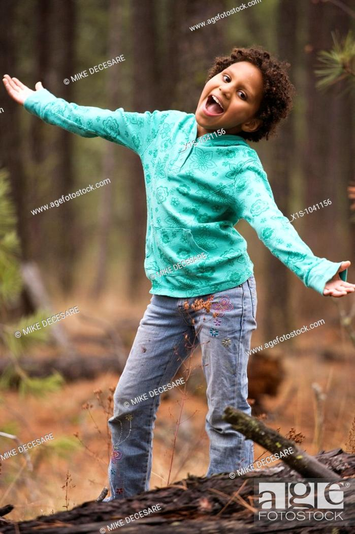 Stock Photo: Young African American child outside in a wooded area with both arms outstretched and she is singing.