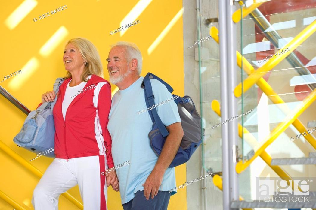 Stock Photo: Senior couple walking up steps with gym bags, smiling, side view.