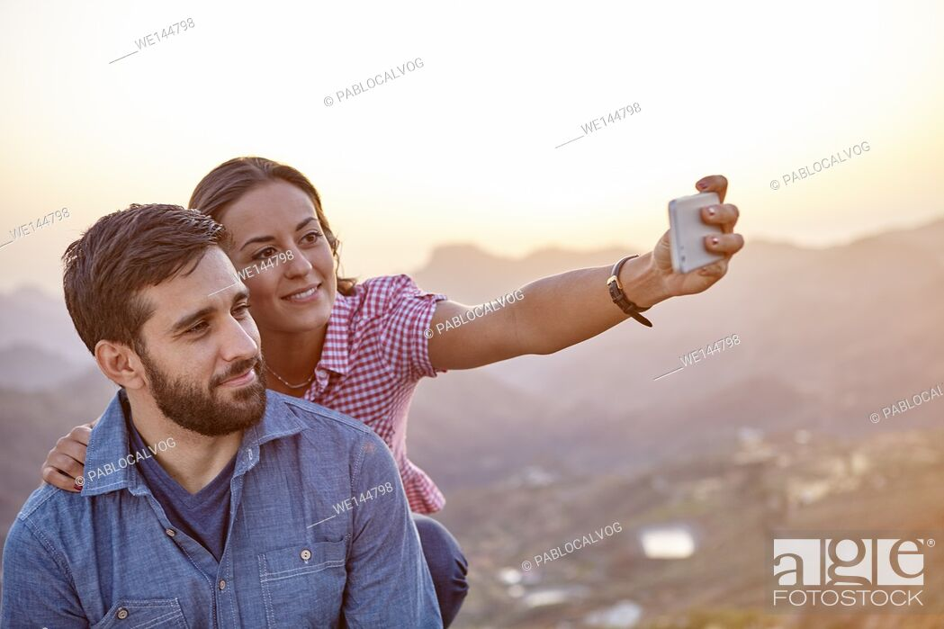 Stock Photo: Happy, smiling young couple taking a selfie on a mountain top with a hazy natural background and wearing casual clothing.