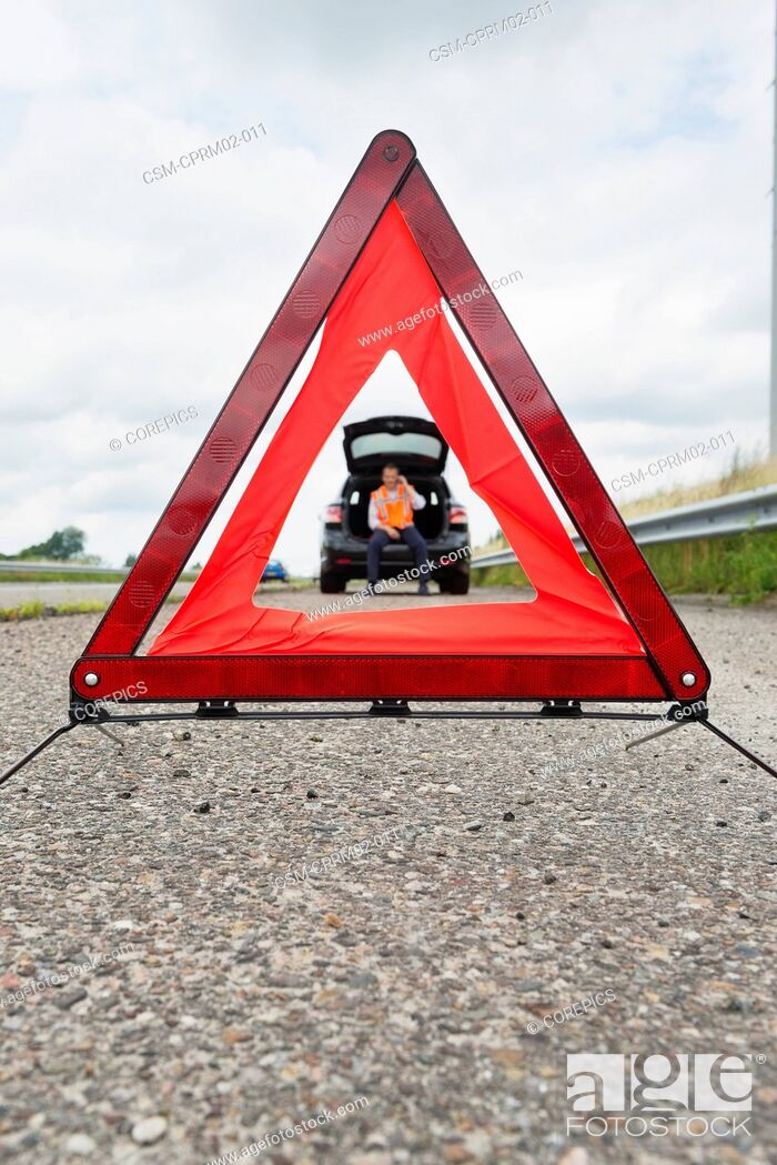 Stock Photo: Warning tiangle on the side of a motorway, with a motorist calling for assistance in the car in the background. Focus on the triangle.