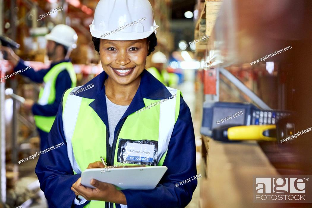 Stock Photo: Portrait smiling female worker with clipboard in distribution warehouse.