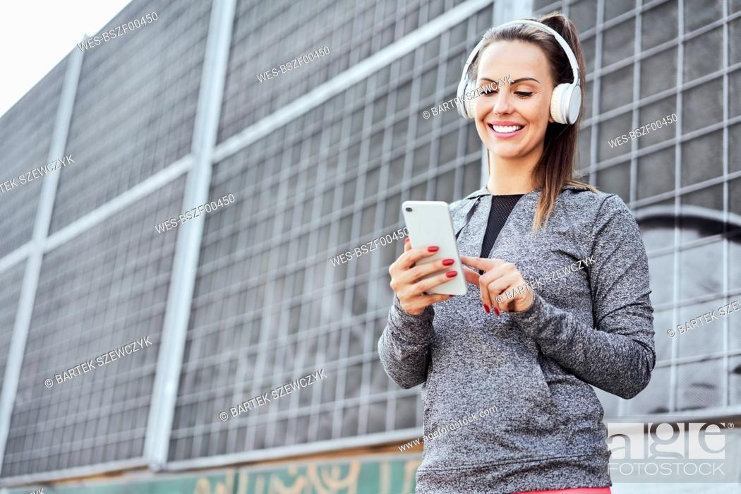 Stock Photo: Woman with headphones using smartphone.