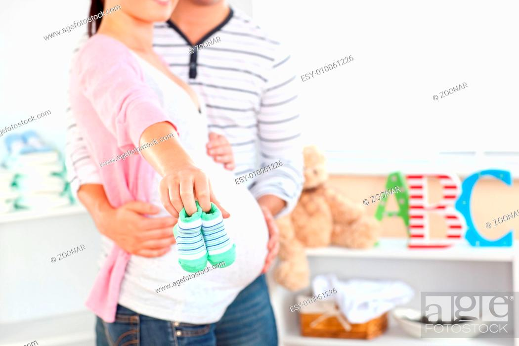 51524bd6a0078 Stock Photo - Close-up of a bright pregnant woman holding baby shoes while  husband touching her belly in the room of their future baby