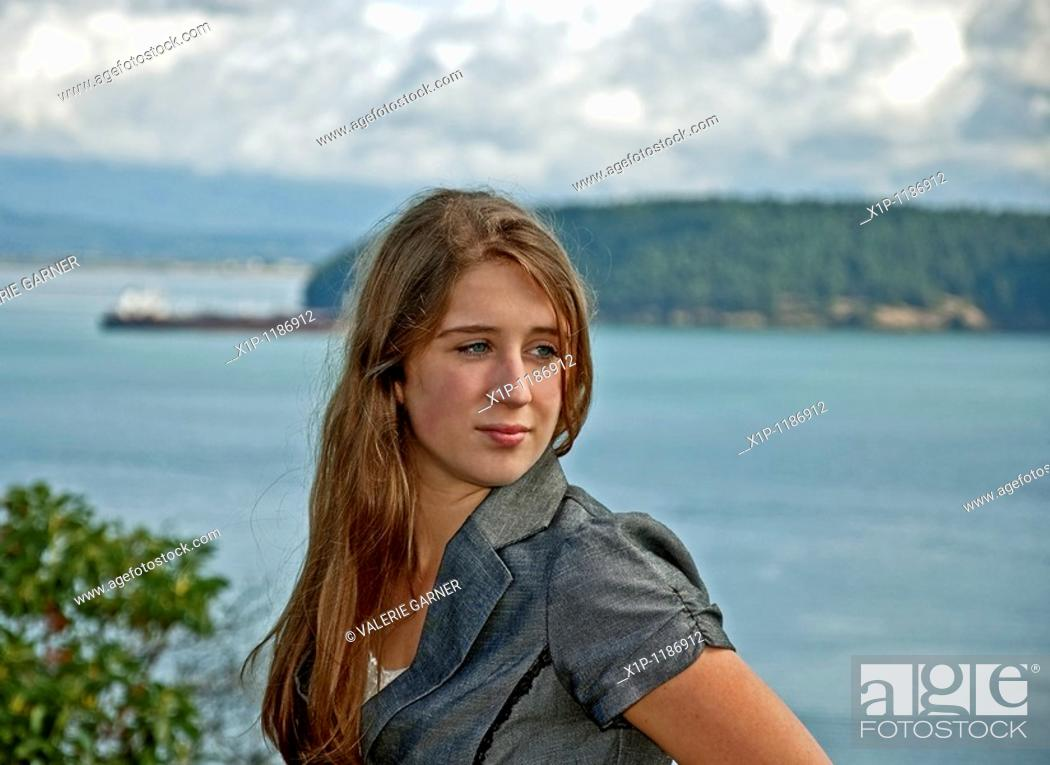 Stock Photo: This pretty green eyed Caucasian, seventeen year old girl is overlooking an ocean scenic with stormy skies and a barge ship out in the distance  She's got long.