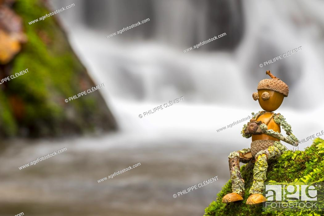 Stock Photo: Figure of little man / photographer made of acorns and twigs sitting on rock next to waterfall along mountain stream in autumn.