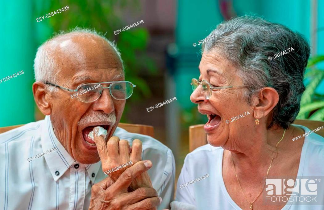 Stock Photo: Elderly couple looking at each other smilingly. The old woman giving meringue cake to the old man.