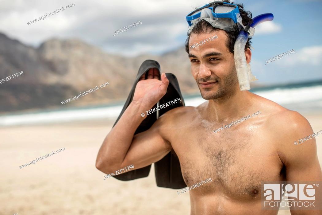 Stock Photo: Young man with snorkeling equipment on the beach.