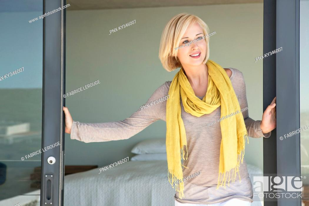 Stock Photo: Woman standing at door and smiling.