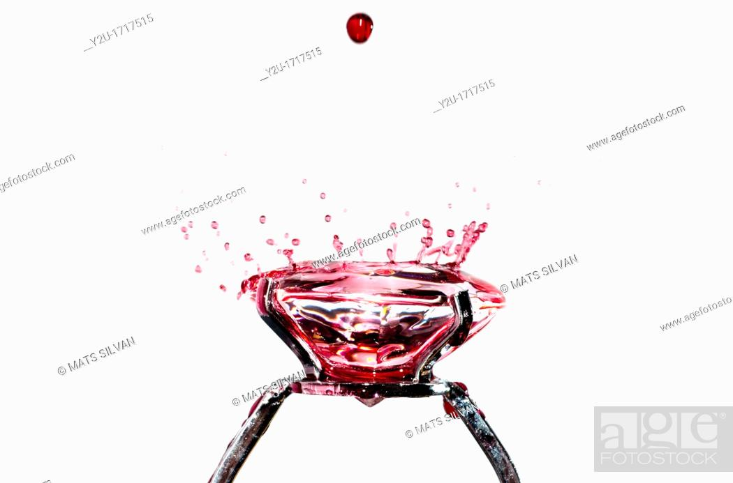 Stock Photo: Red water drops falling on a diamond ring.