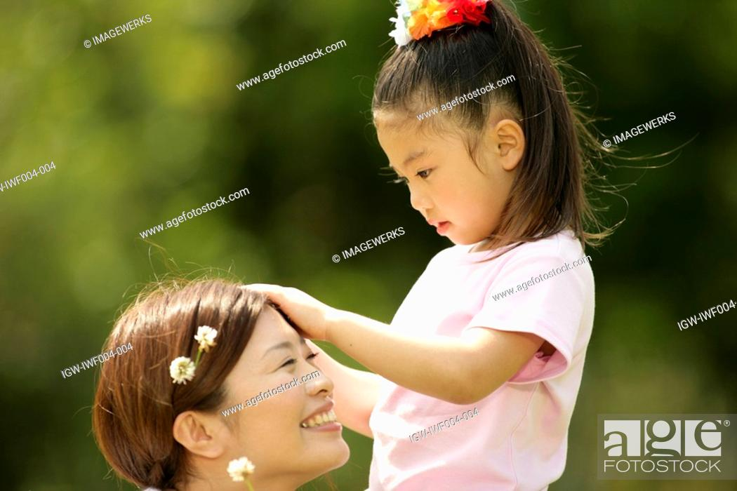 Stock Photo: A young girl putting flowers in the hair of her mother.