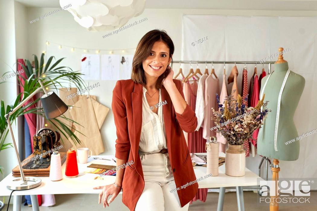 Stock Photo: Confident female fashion designer leaning on desk against clothes rack at atelier.