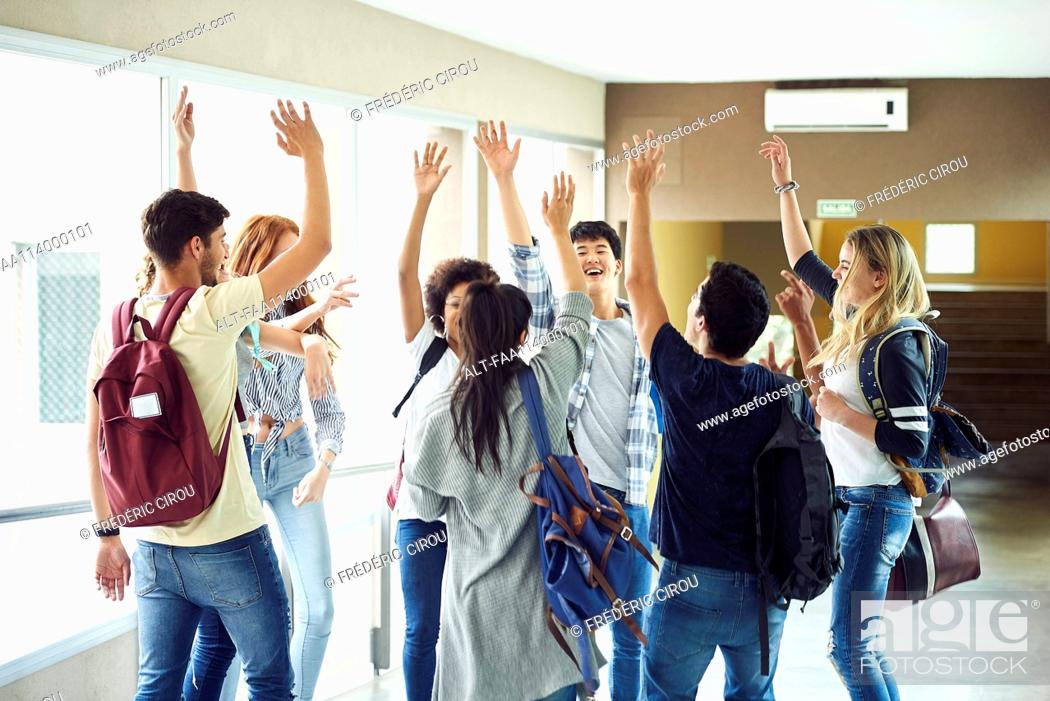 Stock Photo: Group of students standing in circle in corridor with hands raised in the air.
