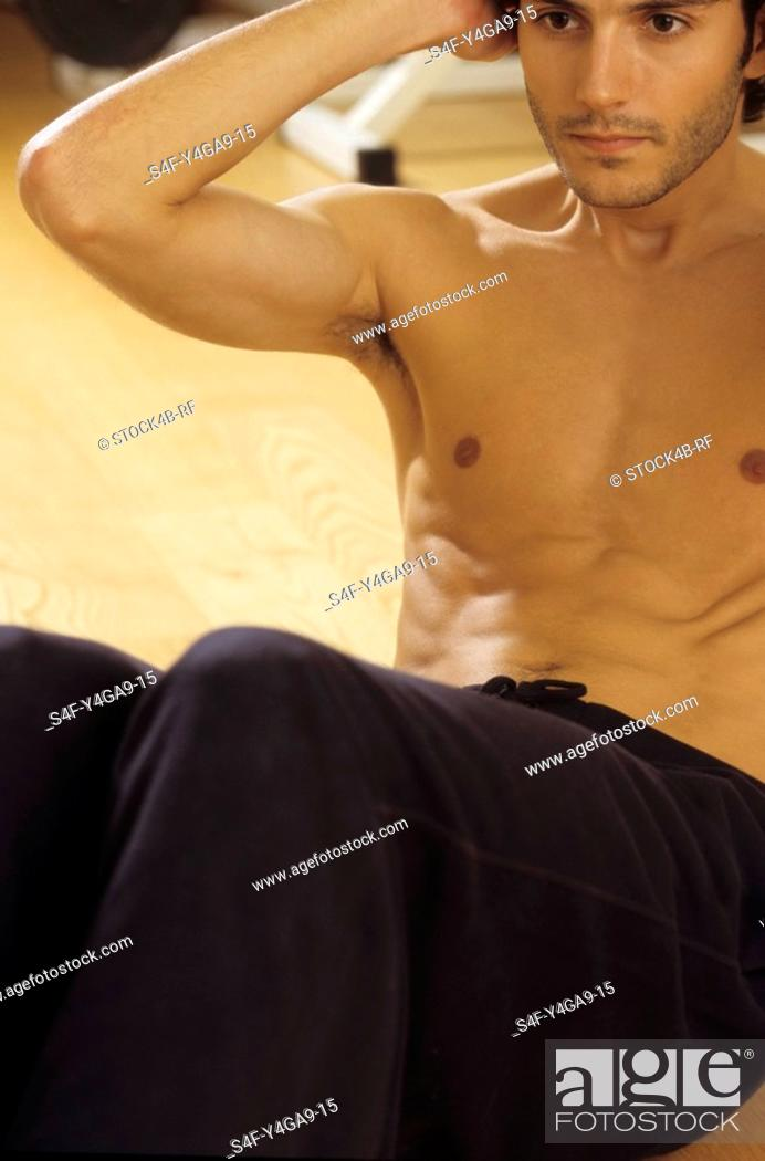 Stock Photo: Darkhaired Man doing Sit-Ups - Physicalness - Sportiness.