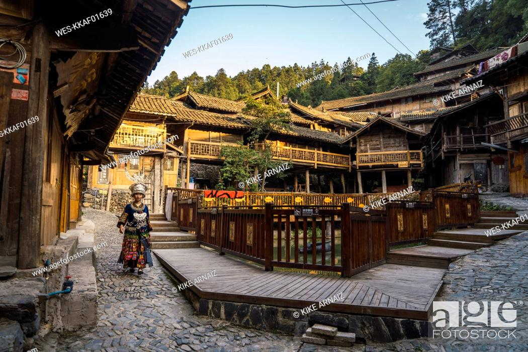 Stock Photo: China, Guizhou, young Miao woman in traditional dress walking in a settlement.