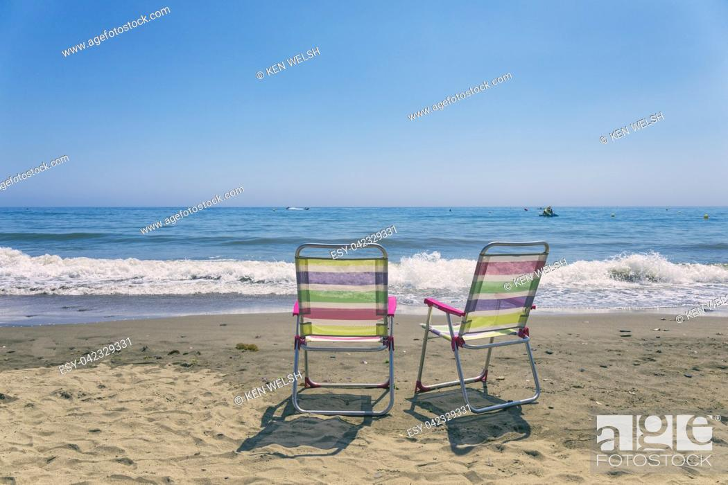 Stock Photo: Two empty chairs on the seashore.