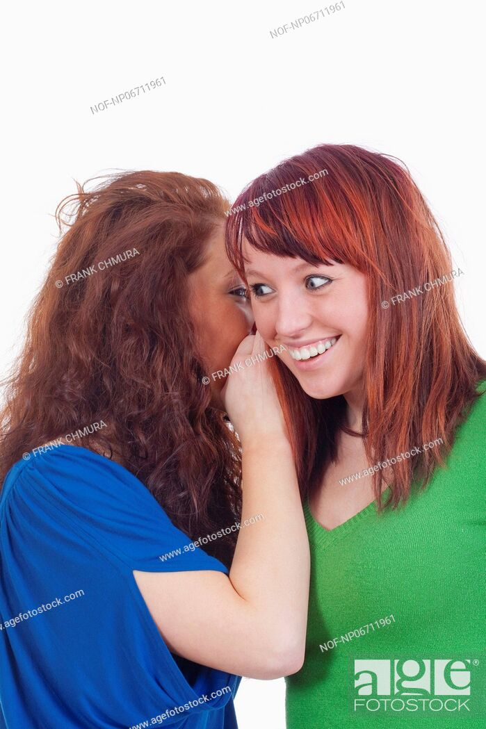 Stock Photo: two young women whispering gossip - isolated on white.
