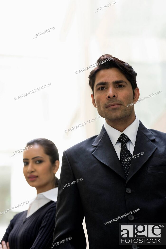 Stock Photo: Businessman in suit in foreground with businesswoman behind.