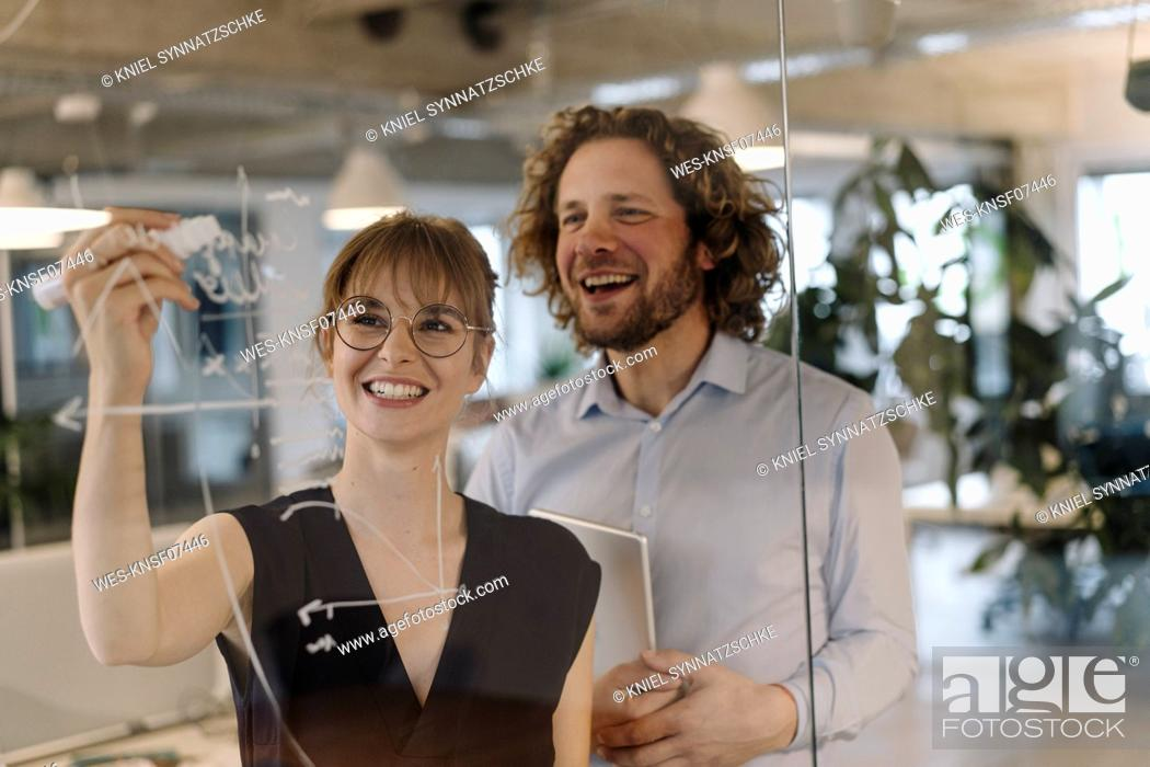 Stock Photo: Happy businessman and businesswoman working on a project in office.