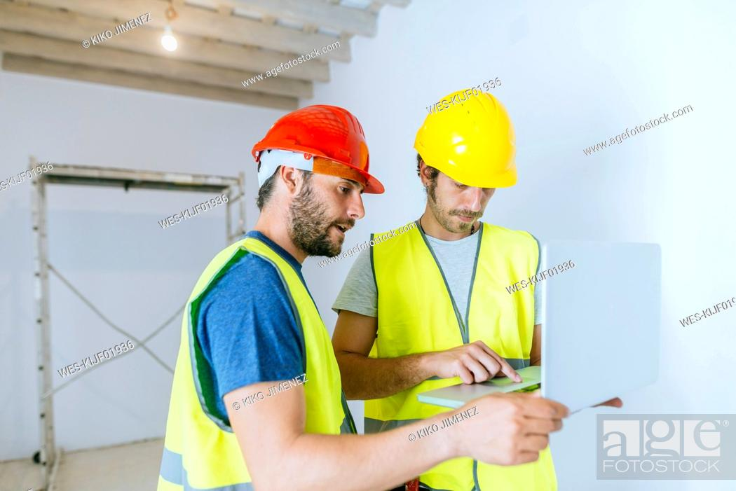 Stock Photo: Workers using laptop at construction site.