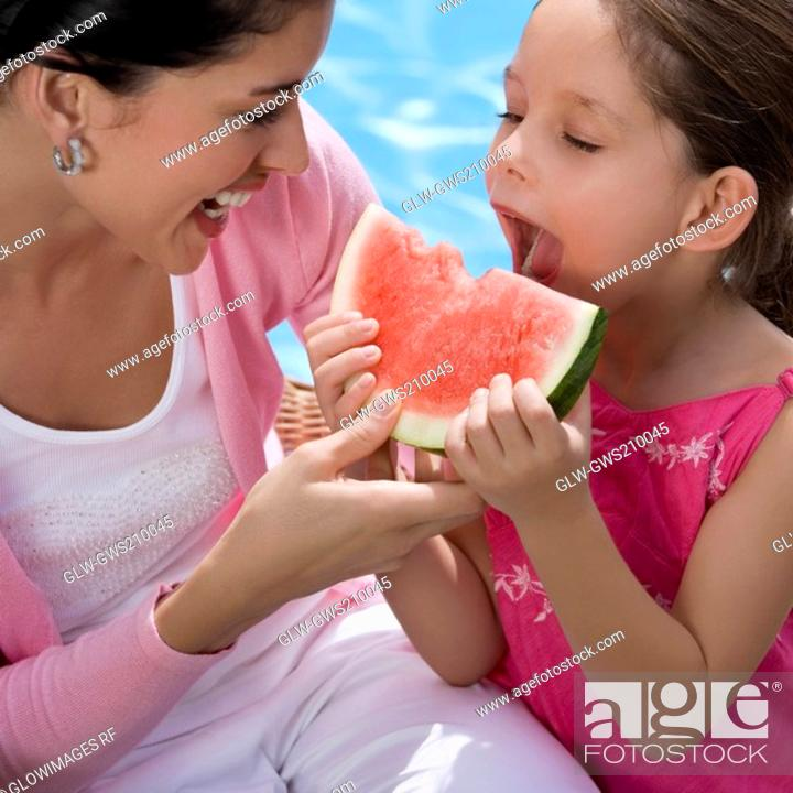 Stock Photo: Close-up of a girl eating a slice of watermelon with her mother laughing.
