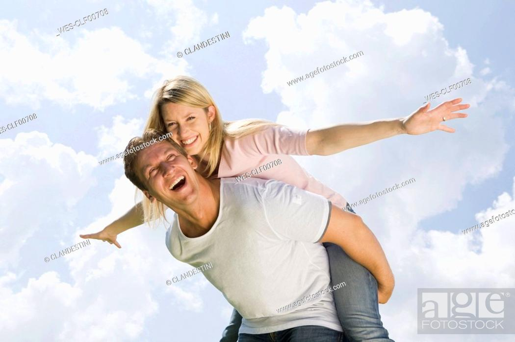 Stock Photo: Germany, Bavaria, Munich, Young man giving piggyback to woman, laughing, portrait.