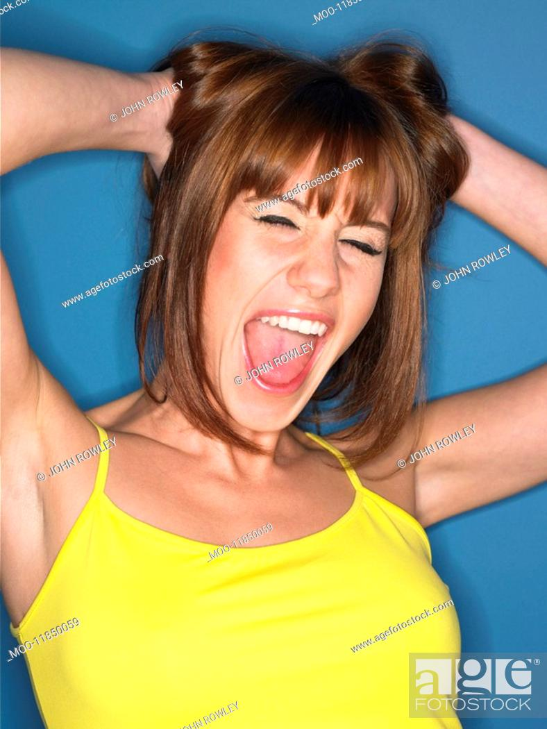Stock Photo: Girl with hands in hair in studio head and shoulders.