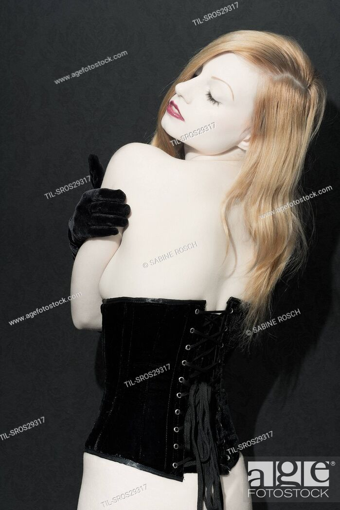 Imagen: Pale red head girl facing camera wearing black lace veil and corset.