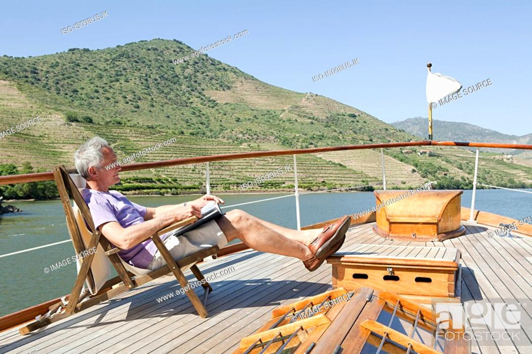 Stock Photo: Senior man reading book on a boat holiday.