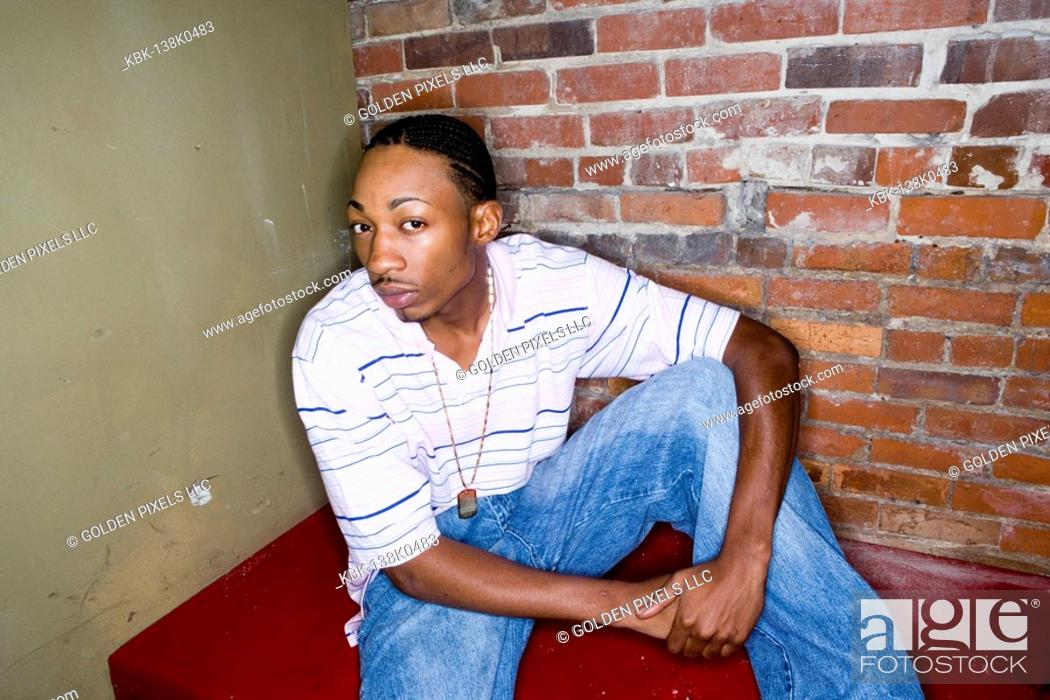 Imagen: Portrait of a young man in hip-hop fashion sitting against brick wall.
