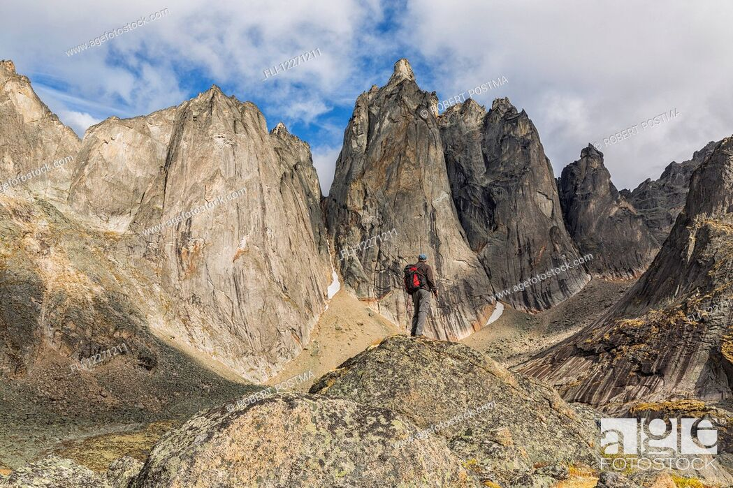Imagen: Man standing on a rock overlooking the granite jagged peaks of Tombstone Territorial Park; Yukon, Canada.