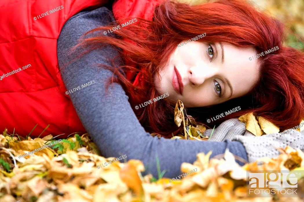Stock Photo: A young woman lying on autumn leaves.