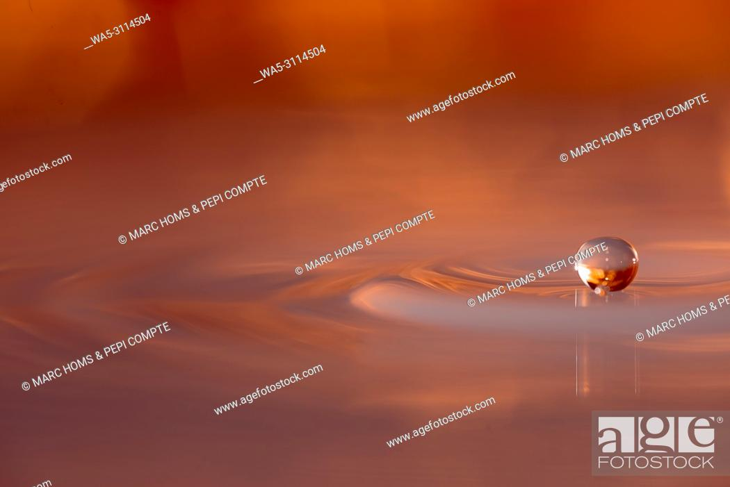 Stock Photo: Copper colored water drop floting above the surface of the water.