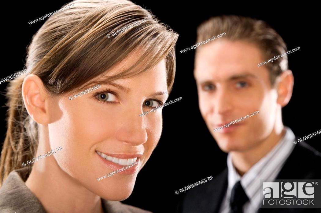 Stock Photo: Portrait of a businesswoman with a businessman behind her.