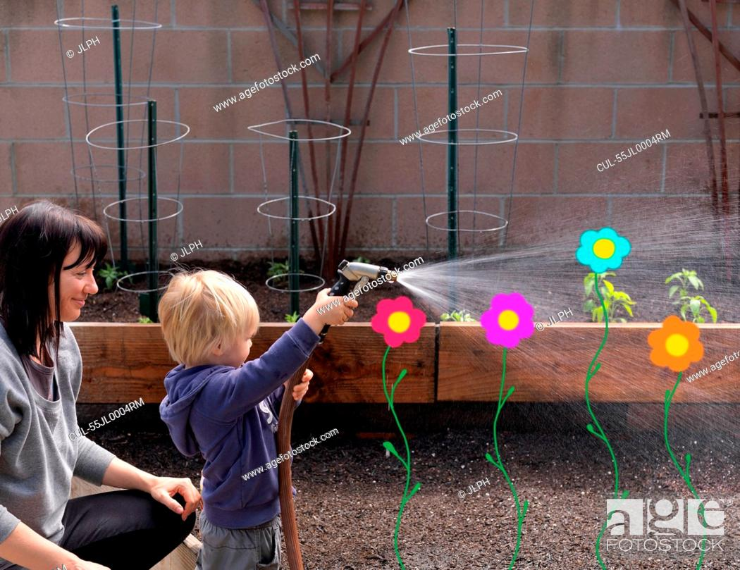 Stock Photo: Mother and son with hosepipe in garden.