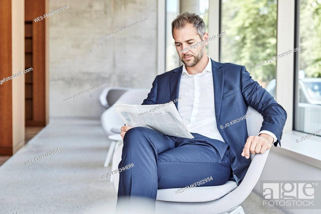 Stock Photo: Businesssman sitting on chair reading newspaper.
