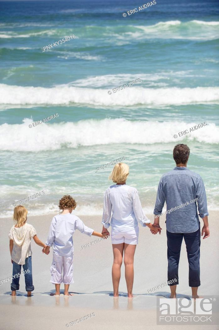 Stock Photo: Couple with two children standing on the beach.