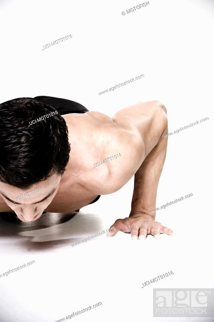 Stock Photo: Bare-chested man doing push-ups.