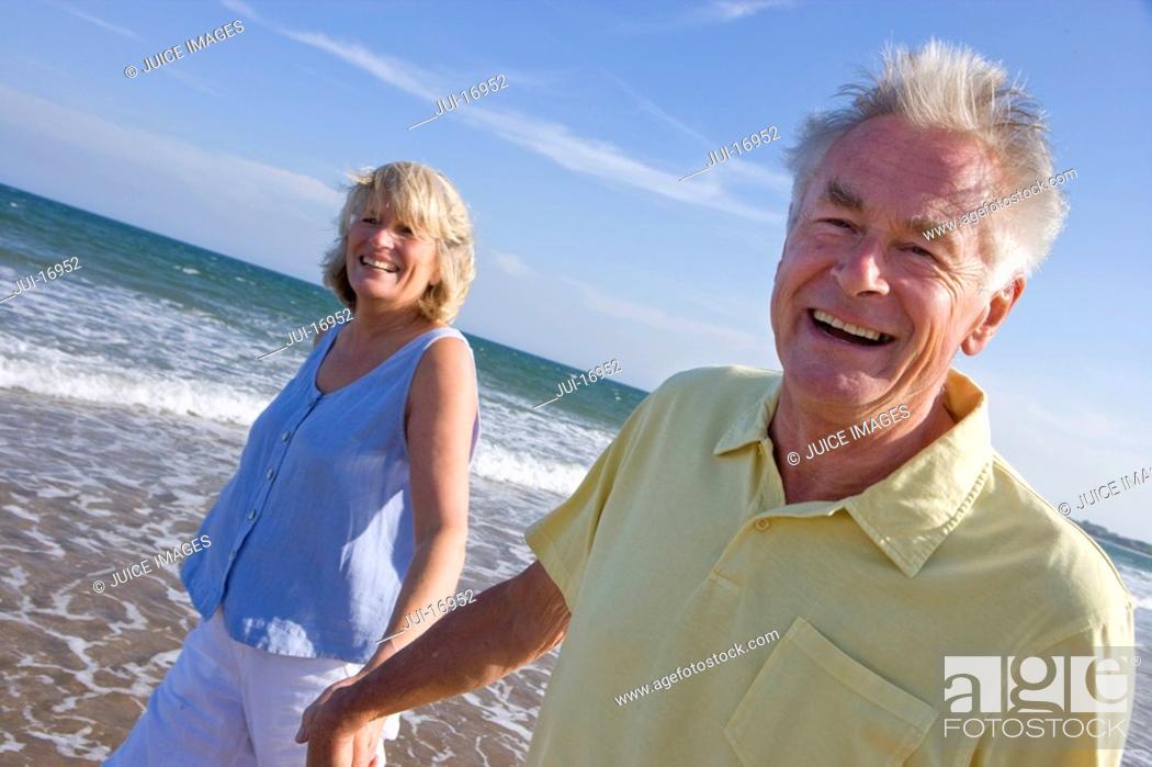 Stock Photo: Portrait of senior couple walking on beach.